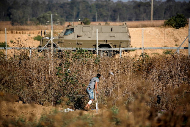 A Palestinian man on crutches watches as an Israeli military vehicle drives past during clashes near the fence along the border with Israel near Bureij in the central Gaza Strip on June 14, 2019. (Photo by Mohammed Abed/AFP Photo)