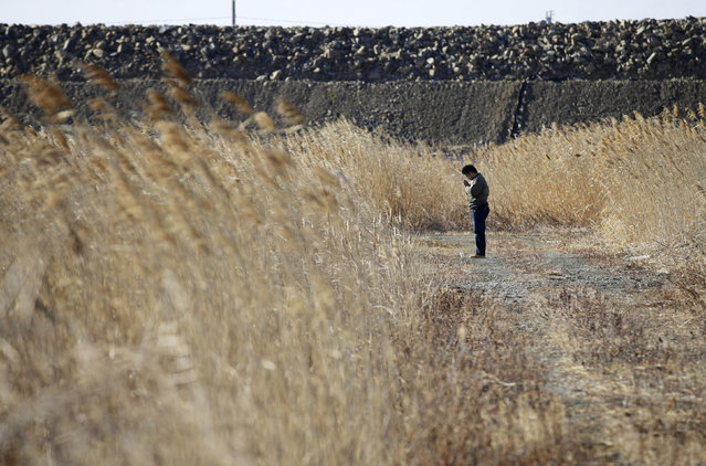 A man offers prayers at the site where a house of his missing colleague once stood, in Ishinomaki, Miyagi prefecture, Japan Saturday, March 11, 2017. On Saturday, Japan is marking the anniversary of the 2011 massive earthquake and tsunami that struck the nation. (Photo by Hiroki Yamauchi/Kyodo News via AP Photo)