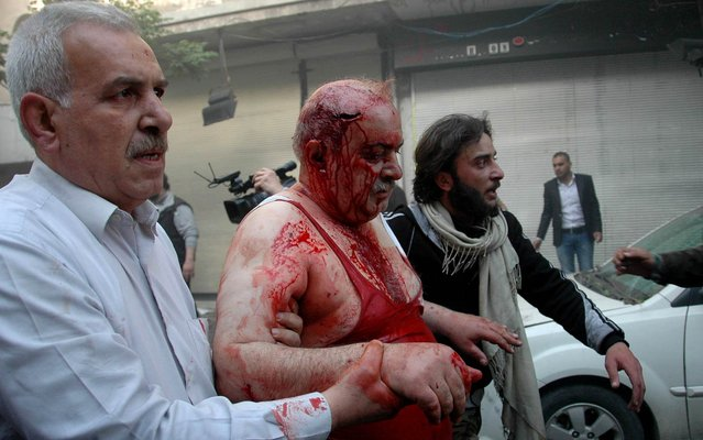 Syrians help a wounded man following a car bomb explosion in al-Khudary Street in the Karm al-Loz neighbourhood of the central Syrian city of Homs on April 9, 2014. More than 150,000 people have been killed in Syria since the conflict began in March 2011, a monitoring group said in a new toll released. (Photo by AFP Photo/STR)