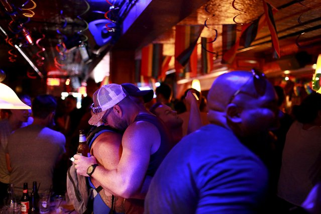 Men embrace as people celebrate inside the Stonewall Inn in the Greenwich Village neighborhood of New York June 26, 2015. (Photo by Eduardo Munoz/Reuters)