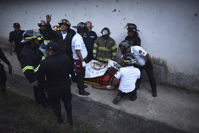 Firefighters surround a man's body inside a reformatory for youth and men during a riot at the Centro Correccional Etapa II in San Jose Pinula, Guatemala, Sunday, March 19, 2017. (Photo by Oliver de Ros/AP Photo)