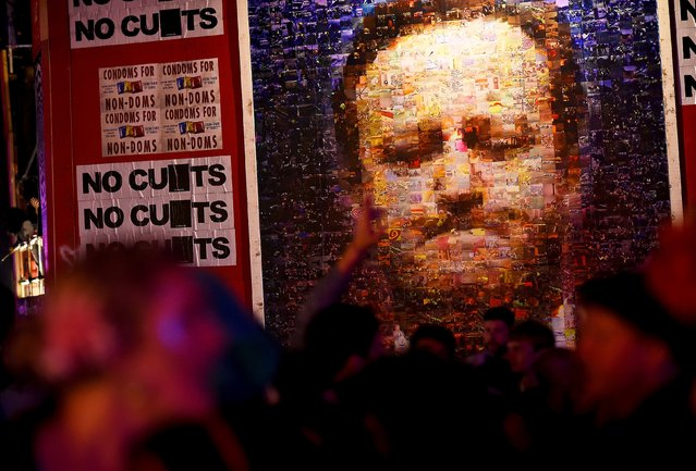 Revellers dance in front of a poster depictng Prime Minister David Cameron at the Shangri La at Worthy Farm in Somerset during the Glastonbury Festival in Britain, June 27, 2015. (Photo by Dylan Martinez/Reuters)