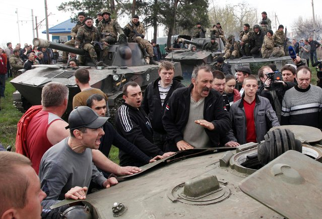 """Pro-Russian activists block a collumn of Ukrainian men riding on Armoured Personnel Carriers in the eastern Ukrainian city of Kramatorsk on April 16, 2014. Ukraine's security service said on April 16 it had intercepted communications showing that Russian commanders in the separatist east had issued pro-Kremlin militants """"shoot-to-kill"""" orders after Kiev launched an operation to oust them. (Photo by Anatoliy Stepanov/AFP Photo)"""