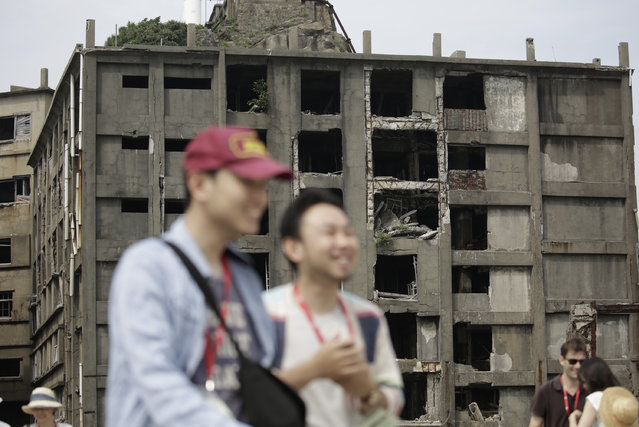 "In this June 29, 2015 photo, forlorn buildings are seen at Hashima Island, commonly known as Gunkanjima, which means ""Battleship Island"", off Nagasaki, Nagasaki Prefecture, southern Japan. (Photo by Eugene Hoshiko/AP Photo)"