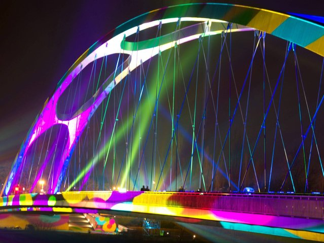 People crosses the illuminated bridge Osthafenbruecke during Luminale festival of light in Frankfurt, Germany, 30 March 2014. The 7th Biennale of Lighting Culture runs from 30 March to 04 April. (Photo by Boris Roessler/EPA)