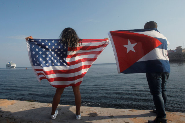 People with Cuban and U.S. flags look at the arrival of U.S. Carnival cruise ship Adonia at the Havana bay, the first cruise liner to sail between the United States and Cuba since Cuba's 1959 revolution, Cuba, May 2, 2016. (Photo by Reuters/Stringer)