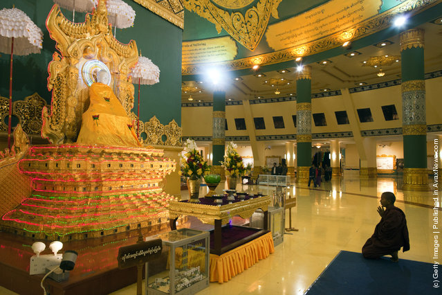 A monk prays inside the hall of the Ouparta Thandi  pagoda which was built to mirror the famous  Shwedagon pagoda