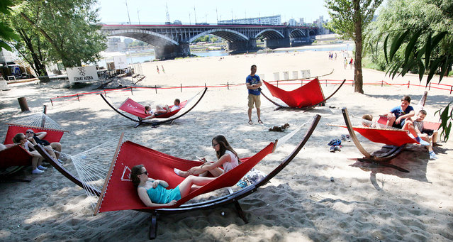 People relax at a beach along the Vistula River as a heat wave in Europe reached Warsaw, Poland, Friday, July 3, 2015. (Photo by Czarek Sokolowski/AP Photo)