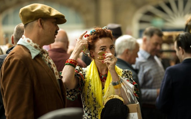 People dressed in period outfits look to buy vintage items from trade stalls as they attend the Vintage By The Sea festival in Morecambe, northwest England on September 1, 2019. The free two-day festival celebrates music, fashion, film, art, design and dance from the 1920s onwards with an emphasis on glamour and style. (Photo by Oli Scarff/AFP Photo)