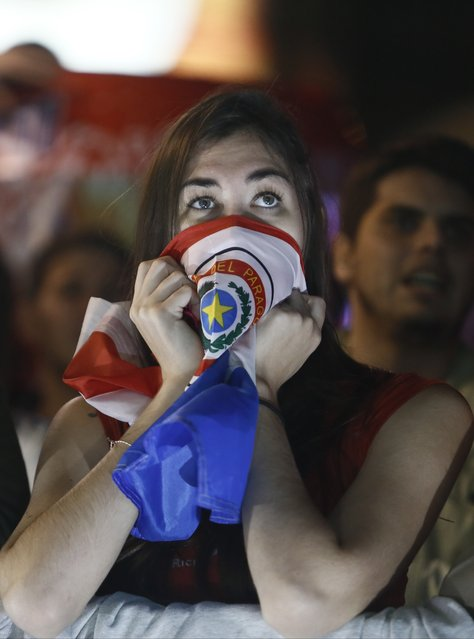 A fan of Paraguay's national soccer team covers her mouth with a Paraguayan flag while watching the Copa America semifinal soccer match between Paraguay and Argentina, on a television screen in Asuncion, Paraguay, Tuesday, June 30, 2015. (Photo by Cesar Olmedo/AP Photo)