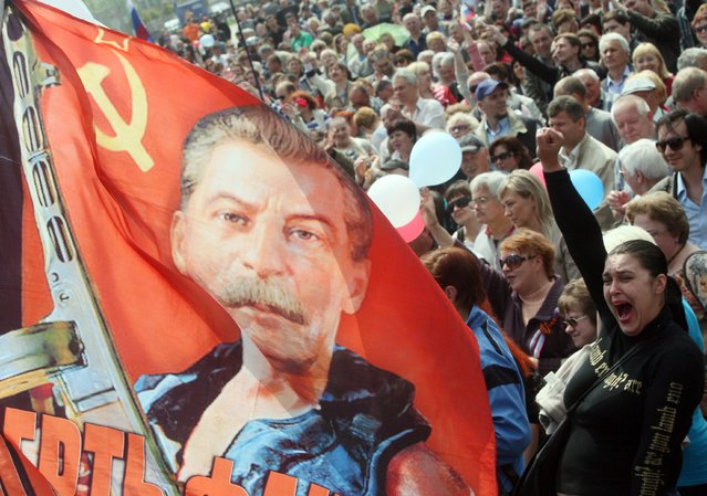 "A pro-Russia activist holds a flag depicting Stalin with a machine gun in his hands reading ""Death to fascism!"" during a rally of the Russian Block marking May Day in the eastern Ukrainian city of Donetsk on May 1, 2014. Some 100,000 workers on May 1 paraded on Red Square for the first time since the 1991 Soviet breakup as the takeover of Crimea triggered a surge of patriotism and boosted Russian President Vladimir Putin's standing. (Photo by Alexander Khudoteply/AFP Photo)"
