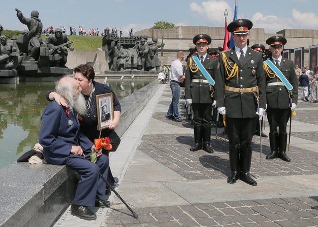 A woman holding a portrait of her relative kisses a WWII veteran as soldiers of the Guard of Honor stand by at the WWII memorial in Ukraine's capital Kiev. Ukrainians marked the 71st anniversary of the victory over Nazi Germany. May 9, 2016. (Photo by Efrem Lukatsky/AP Photo)