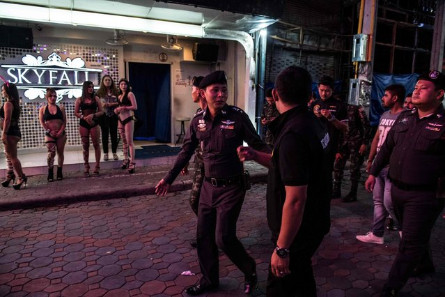 "This photo taken on March 29, 2017 shows Thai Police Lieutenant Colonel Sulasak Kalokwilas (C) leading a group of policemen and soldiers past young women (L) enticing customers to enter a bar, as they patrol Walking Street in Pattaya. Thai tourism chiefs have vowed to clean up their ""Sin City"" by transforming it into a family-friendly Happy Zone. Earlier this month governor Pakkaratorn Teianchai said: ""I want people to see that we are not like what they say. We are not allowing prostitution in these entertainment places"". But these pictures show that Thai police and tourism chiefs still have a long way to go. More than a million men flock to its red light district each year and almost 20 per cent of the population are employed in the s*x trade. The number of female s*x workers in Thailand was put at more than 120,000 in a 2014 UNAIDS report. Some estimates run to double that and not all the women who get paid for s*x are full-time prostitutes. (Photo by Roberto Schmidt/AFP Photo)"