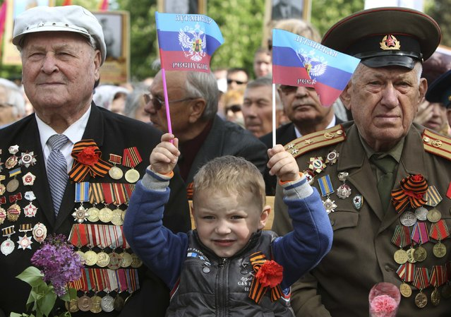 """A child holds flags, which read """"Lugansk Republic"""", as he marks Victory Day with former Soviet servicemen during celebrations in the Eastern Ukrainian city of Lugansk May 9, 2014.  Russian President Vladimir Putin praised the Soviet role in defeating fascism on Friday, the anniversary of the World War Two victory over Nazi Germany, and said those who defeated fascism must never be betrayed. (Photo by Valentyn Ogirenko/Reuters)"""