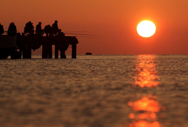 A picture taken late on May 4, 2014, shows people fishing during sunset in the Crimean town of Alushta. (Photo by Yuriy Lashov/AFP Photo)