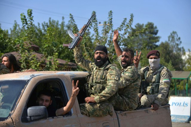 Members of Syrian National Army, known as Free Syrian Army, wave as they drive to cross into Syria near the Turkish border town of Ceylanpinar in Sanliurfa province, Turkey, October 10, 2019. (Photo by Reuters/Stringer)