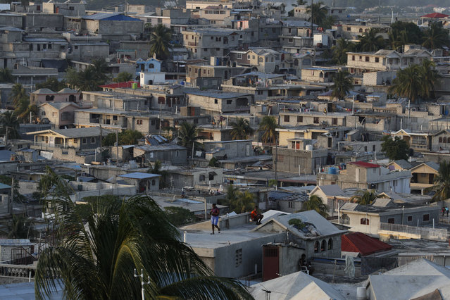 People pass the time on rooftops as afternoon turns to evening in Port-au-Prince, Haiti, Tuesday, October 8, 2019. Haiti has entered its fourth week of anti-government protests that have paralyzed the economy and shuttered schools as demonstrators demand the resignation of President Jovenel Moise. (Photo by Rebecca Blackwell/AP Photo)
