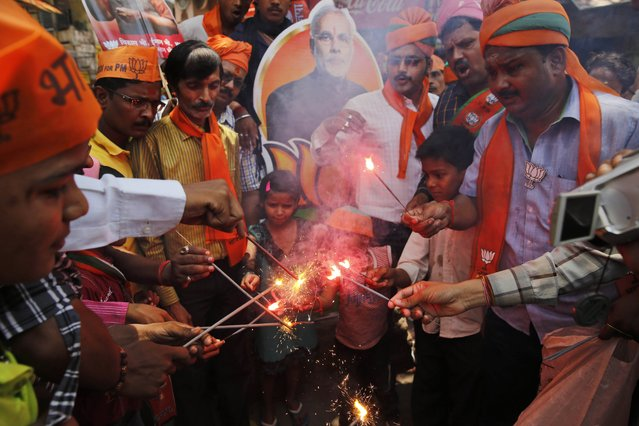 Bharatiya Janata Party (BJP) supporters light firecrackers to celebrate the party's winning performance in the general elections in Varanasi, in the northern Indian state of Uttar Pradesh, Friday, May 16, 2014.  (Photo by Rajesh Kumar Singh/AP Photo)