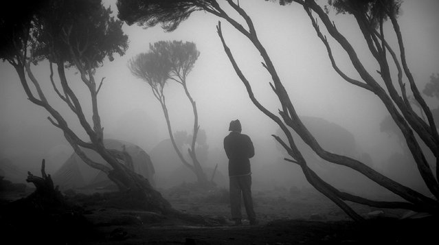 """Fog"". December 22, 2012 – A porter relaxes after arriving at Shira Camp at the end of a day of climbing one section of Mount Kilimanjaro. Photo location: Shira Camp, Kilimanjaro, Tanzania. (Photo and caption by Andrew Prince/National Geographic Photo Contest)"
