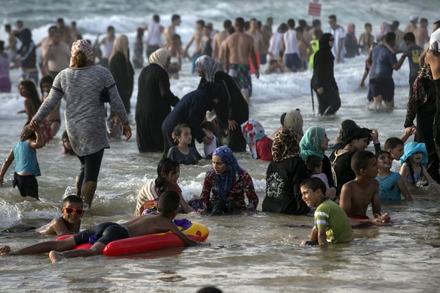 Muslims, most from the West Bank and East Jerusalem, enjoy the water at a beach of the Mediterranean in Tel Aviv during Eid al-Fitr, which marks the end of the holy month of Ramadan July 19, 2015. (Photo by Baz Ratner/Reuters)