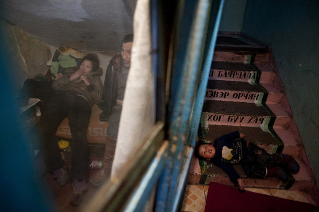Asia, Mongolia, Ulaan Baator, March 10, 2011. Jigjjav family taken in the space of few meters square under the staircase where they live. In the small room the former shepherd Argalshikhan Jigjjav and his pregnant daugther Dyun Erdene, 26 years old and his nephew Aztardal 4 years old is playinfg on the stair. They used to live with in Gobi-Ugtaal in the Dunggobi province, but during the Dzud they lost their 150 animals and, therefore, they decided to move to the city. (Photo by Alessandro Grassani)