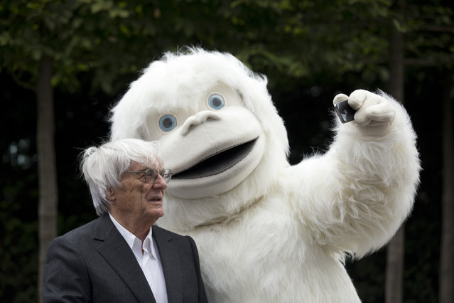Formula One boss Bernie Ecclestone has a selfie taken with a person dressed in a Yeti costume during a photocall to promote the Mongol Rally outside the headquarters of Formula One Group in London, Thursday, July 16, 2015. (Photo by Matt Dunham/AP Photo)