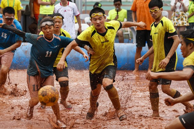 Players from two opposing teams compete in the 'Swamp Soccer China' tournament at a sports complex in Beijing, China, July 26, 2015. A total of 32 teams is participating in this year's 'Swamp Soccer China' tournament, which is played for 24 minutes on a mud field with a six players per side. (Photo by Rolex Dela Pena/EPA)