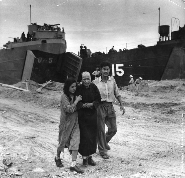 A civilian casualty arrives on the beach at Inchon in South Korea to see the US medical officer during the Korean War. US amphibious craft used in the invasion are in the background