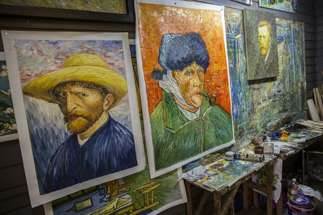 Copies of paintings by Van Gogh can be seen in a gallery at the artist village on June 12, 2014 in Shenzhen, China. The Dafen Artist Village in Guangdong province, China, is home to thousands of artists who reproduce some of the world's most iconic paintings as well as create their own works. The village, on the outskirts of Shenzhen, is becoming a major center for original Chinese art. (Photo by Palani Mohan/Getty images)