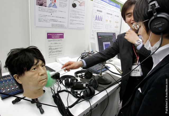 "At the NTT Research and Development Forum in Tokyo on February 22, 2011, a staff member tickles the ear of a robot to demonstrate ""tactile illusions"" – simulations of ticklishness relayed by sound signals"