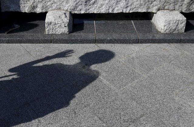 A visitor casts a shadow on the ground at Peace Park in Nagasaki, southwestern Japan, July 31, 2015. (Photo by Issei Kato/Reuters)