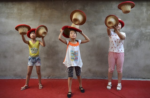 Students toss hats as they practice at an acrobatic school in Sanwang village, Anhui province, China, July 31, 2015. (Photo by Reuters/Stringer)