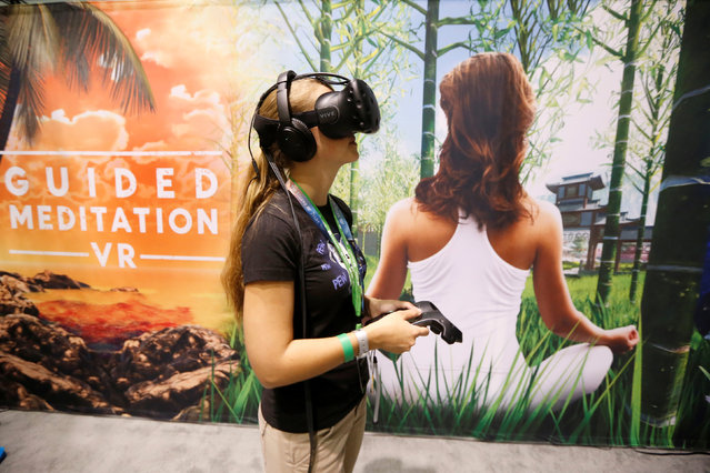 A woman uses a virtual reality headset to play a guided meditation video game at the E3 Electronic Expo in Los Angeles, California, U.S. June 14, 2016. (Photo by Lucy Nicholson/Reuters)