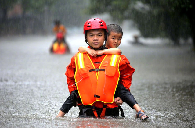 A Chinese rescuer evacuates a young boy from flooded areas caused by heavy rains in Changsha city, central China's Hunan provincehangsha, capital of Hunan on July 3, 2017. (Photo by Imaginechina/Rex Features/Shutterstock)
