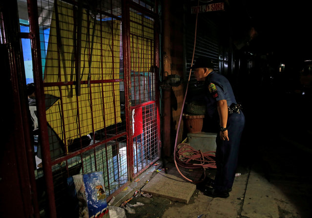 """A member of the Philippine National Police looks through the gate of a computer rental shop during  the """"Rid the Streets of Drinkers and Youth"""" operation in Las Pinas city, metro Manila, Philippines June 1, 2016. (Photo by Romeo Ranoco/Reuters)"""