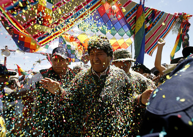 Bolivia's first indigenous president Evo Morales greets supporters upon his arrival to Caracollo town, some 190 km (118 miles) south of La Paz October 13, 2008. (Photo by David Mercado/Reuters)
