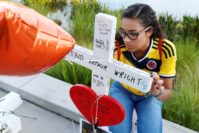 A youth signs the back of one of 49 wood crosses used to commemorate the victims of the Pulse night club shooting in Orlando, Florida, U.S., June 17, 2016. (Photo by Carlo Allegri/Reuters)