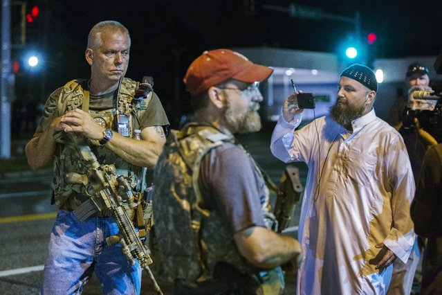 Members of the Oath Keepers walk with their personal weapons on the street during protests in Ferguson, Missouri August 11, 2015. (Photo by Lucas Jackson/Reuters)