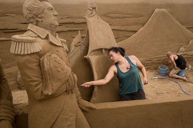 Sand sculptors Sue McGrew of the USA (L) and Leonardo Ugolini of Italy work on the American/ Japan section of a large sand sculpture at the site of Yokohama Sand Art Exhibition – Culture City of East Asia 2014 on July 16, 2014 in Yokohama, Japan. Producer and sand sculptor Katsuhiko Chaen invited artists from around the world including South Korea and China, to recreate the World Heritage and historical buildings in China, Japan and South Korea. The exhibition will be open from July 19 to November 3, 2014. (Photo by Chris McGrath/Getty Images)