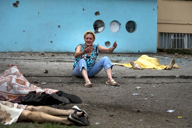 A woman cries near the bodies of people, among whom were family members, who were killed during shelling by Ukrainian government troops in Luhansk, eastern Ukraine, on Jule 18, 2014. The fighting between the government and pro-Russia separatists in Luhansk continued as world leaders called for an immediate cease-fire in eastern Ukraine and demanded speedy access for international investigators to the crash site of the Malaysia Airlines jetliner shot down over the country's battlefields. (Photo by Mikhail Ivanchenko/Associated Press)