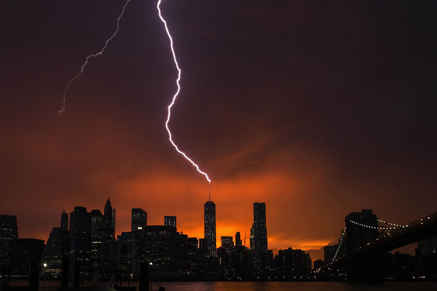 Lightning strikes One World Trade Center in Manhattan as the sun sets behind the city after a summer storm in New York, on Jule 3, 2014. (Photo by Lucas Jackson /Reuters)