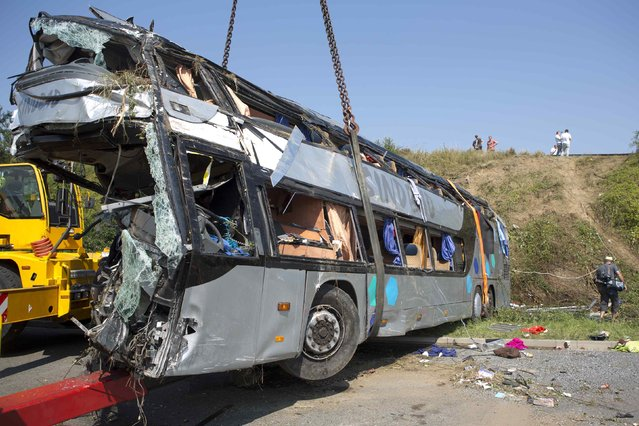 A crashed bus is loaded on a platform at the site of the accident on German A2 highway near the eastern city of Dresden July 19, 2014. A bus from Poland crashed at around 02:00 am into another bus from Ukraine, killing at least nine and injuring some 43 people, local media and German police said. (Photo by Axel Schmidt/Reuters)