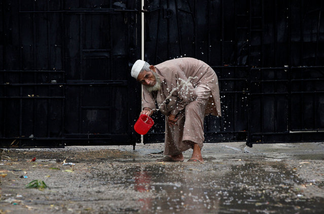 A man clears water from the entrance of an office after rain in Karachi, Pakistan, June 29, 2016. (Photo by Akhtar Soomro/Reuters)