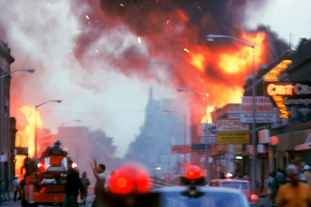 View along a street where buildings burn on both sides during riots in Detroit, Michigan, late July 1967. Police and firefighters are visible on the street. (Photo by Declan Haun/The LIFE Picture Collection/Getty Images)
