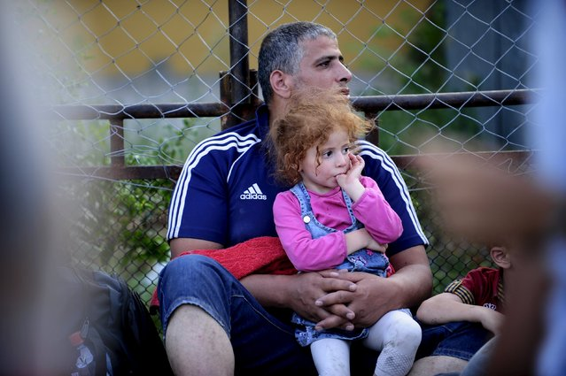 A migrant holds his daughter at Gevgelija railway station August 19, 2015. Thousands of migrants kept up the wait on Wednesday in a small Macedonian town in the hope of travelling onwards to Western Europe. After days of crowds overwhelming the small station at Gevgelija, Macedonian authorities have established special trains for migrants from south to the northern border with Serbia. (Photo by Ognen Teofilovski/Reuters)