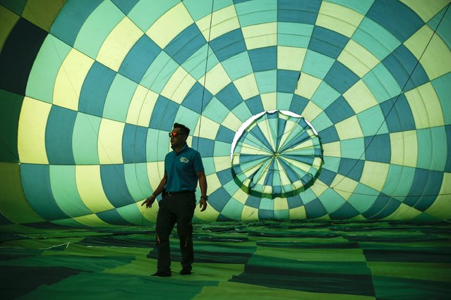 A staff memeber inspects the interior of a hot air balloon during the 2016 International Hot Air Balloon Festival in Taitung, southeast of Taiwan, 01 July 2016. (Photo by Ritchie B. Tongo/EPA)