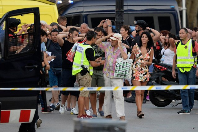 """Policemen check the identity of people standing with their hands up after a van ploughed into the crowd, killing two persons and injuring several others on the Rambla in Barcelona on August 17, 2017. A driver deliberately rammed a van into a crowd on Barcelona' s most popular street on August 17, 2017 killing at least two people before fleeing to a nearby bar, police said. .Officers in Spain' s second- largest city said the ramming on Las Ramblas was a """"terrorist attack"""" and a police source said one suspect had left the scene and was """"holed up in a bar"""". The police source said they were hunting for a total of two suspects. (Photo by Josep Lago/AFP Photo)"""