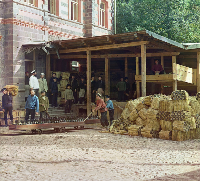 Photos by Sergey Prokudin-Gorsky. Distributing of mineral water. Borzhom (Men pushing carts laden with bottles while others stand and watch; to the side are bundles of packed bottles). Russia, Tiflis province, Gori district, Borjomi, 1912