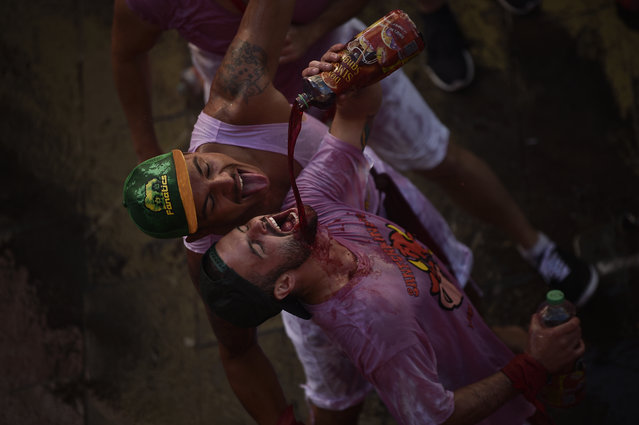 """Revelers drink, during the launch of the """"Chupinazo"""" rocket, to celebrate the official opening of the 2016 San Fermin Fiestas, in Pamplona, northern Spain, Wednesday, July 6, 2016. Revelers from around the world kick off the festival with a messy party in the Pamplona town square, one day before the first of eight days of the running of the bulls. (Photo by Alvaro Barrientos/AP Photo)"""