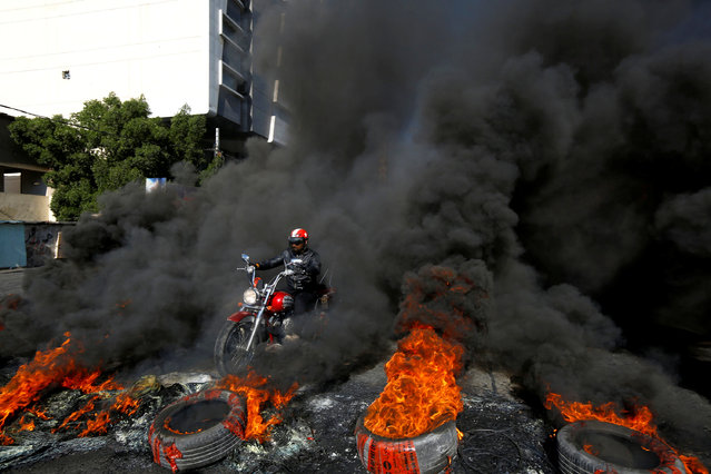 A man rides a motorcycle between burning tires during ongoing anti-government protests in Najaf, Iraq on January 20, 2020. (Photo by Alaa al-Marjani/Reuters)
